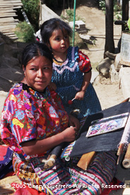 Julia Lopez follows a printed pattern as she weaves in the family compound with her youngest daughter nearby.  Julia, 19, had her first child at age 11.  Photo by Cheryl Guerrero 2005.