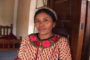 María Sanchez, mother of 8, wears a cinta or ribbon around her head and a huipil typical of her community.  Both are hand woven. María has taught all her daughters the art of weaving their own clothes.