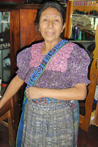 Maximina Yojcon works with a small weavers' group in San Pedro La Laguna and sells their products.  The belt over her shoulder was woven by María Ixmataj with a maguey weft for stiffness, and was beaded by María Gonzales.  Photo by Denise Gallinetti 2005.