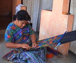 Esperanza Lopez clips dangling supplementary weft threads from a huipil or blouse panel woven on a back strap loom in the style of her community.  Photo by Beth Riley 2005.