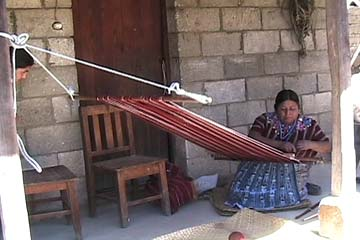 Gregoria Rucuch Cumes sets up her backstrap loom to weave the dark red cloth used in a Patzún-style huipil.  Photo by Kathleen Mossman Vitale 2005.