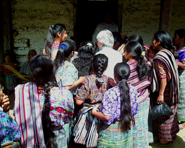 Videotaping weavers in indigenous communities is both a joy and a challenge.  In San Juan Cotzal local weavers excitedly crowd around to peek at the viewfinder when the camera is focused on the weaver's hands.  Photo by Paul G. Vitale 2005.