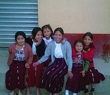 Schoolgirls in Nebaj giggle with embarrassment after begging to be photographed.  The Peace Accord of 1996 gave indigenous children the right to wear traje to school, though in large cities few do.  Photo by Kathleen Mossman Vitale 2005.