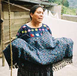 Doña Flor Xoc, president of Nu'Kem Association of Weavers in Tactic and Tamahú in Alta Verapaz, shows off a heavy cotton huipil she wove several years ago.  Photo by Margot Blum Schevill 2005.