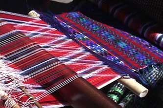 Santiaga weaves a heavily brocaded huipil panel using red and white warps.  Photo by Kathleen Mossman Vitale 2005.